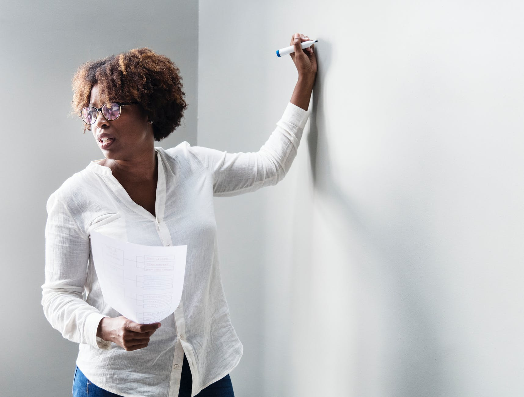 woman writing in white board